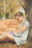 Muchacha adolescente triste en parque del otoño con la libreta Imagen de archivo libre de regalías