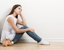 Muchacha adolescente triste en piso Imagen de archivo libre de regalías