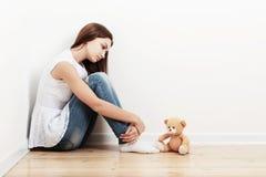 Muchacha adolescente triste en piso Imagenes de archivo