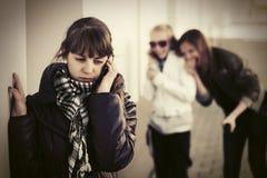 Muchacha adolescente triste que invita al teléfono celular en la pared Foto de archivo libre de regalías