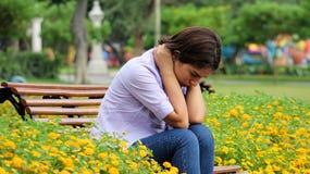 Muchacha adolescente triste que se sienta en parque Foto de archivo