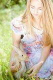 Muchacha adolescente y conejo de la mujer joven el verano al aire libre Foto de archivo libre de regalías