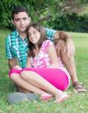 Muchacha adolescente y su padre que se sientan en la hierba en un par hermoso Fotos de archivo