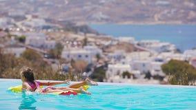 Muchacha adorable con el colchón de aire inflable en la ciudad al aire libre de Mykonos del fondo de la piscina almacen de metraje de vídeo