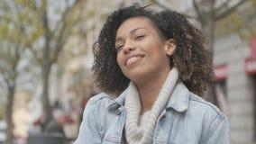 Muchacha adorable con el corte de pelo afro que se sienta en banco en la calle de la ciudad metrajes