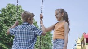 Muchacha adorable con el pelo largo que balancea en un muchacho lindo del oscilación al aire libre Par de niños felices Niños des metrajes