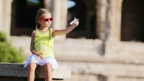 Muchacha adorable con el pequeño fondo Colosseum del aeroplano modelo del juguete en Roma, Italia almacen de video
