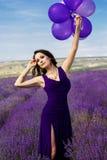 Muchacha adorable con los globos púrpuras foto de archivo libre de regalías