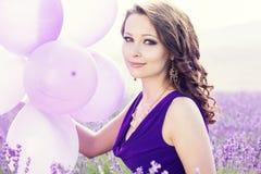 Muchacha adorable con los globos púrpuras imagenes de archivo