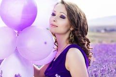 Muchacha adorable con los globos púrpuras imagen de archivo