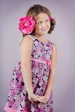 Muchacha adorable con una flor rosada en su pelo Imagenes de archivo
