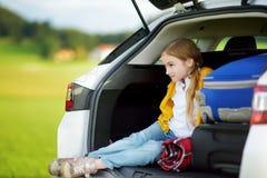 Muchacha adorable con una maleta lista para ir el vacaciones con sus padres Niño que mira adelante para un viaje por carretera o  Imagen de archivo libre de regalías