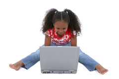 Muchacha adorable de seis años que se sienta en suelo con el ordenador portátil fotografía de archivo