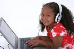 Muchacha adorable de seis años que se sienta en suelo con el ordenador portátil Foto de archivo libre de regalías