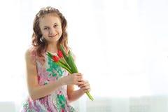 Muchacha adorable del adolescente que se sienta en la ventana con los tulipanes Fotos de archivo
