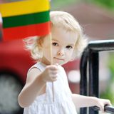 Muchacha adorable del niño con el indicador lituano imagen de archivo