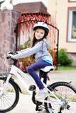 Muchacha adorable del niño en el casco azul que monta su bici Foto de archivo