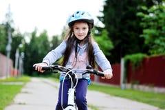 Muchacha adorable del niño en el casco azul que monta su bici Fotos de archivo libres de regalías