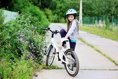 Muchacha adorable del niño en el casco azul que monta su bici Imágenes de archivo libres de regalías
