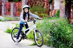 Muchacha adorable del niño en el casco azul que monta su bici Fotografía de archivo libre de regalías