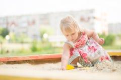 Muchacha adorable del niño en juego de la alineada con la arena Fotografía de archivo