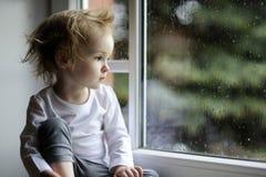 Muchacha adorable del niño que mira las gotas de agua imagen de archivo libre de regalías
