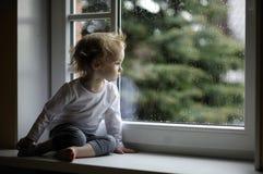 Muchacha adorable del niño que mira las gotas de agua imagen de archivo