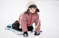 Muchacha adorable del niño sledding en nieve en un platillo Imágenes de archivo libres de regalías