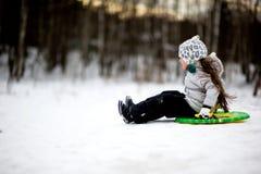 Muchacha adorable del niño sledding en nieve en un platillo Imagen de archivo libre de regalías