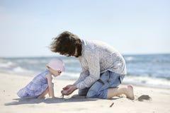 Muchacha adorable del niño y su padre en una playa Fotos de archivo