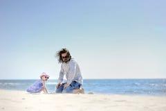 Muchacha adorable del niño y su padre en una playa Imagen de archivo libre de regalías