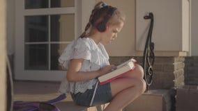 Muchacha adorable durante las vacaciones de verano que se sientan en el patio cerca de casa que escucha la música, cantando y lib almacen de metraje de vídeo