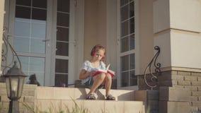 Muchacha adorable durante las vacaciones de verano que se sientan en el patio cerca de casa que escucha la música, cantando y lib almacen de video