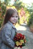 Muchacha adorable en un sobretodo en un rato del día Fotografía de archivo