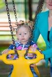 Muchacha adorable feliz del niño en el oscilación en patio cerca de la guardería Montessori Imagen de archivo