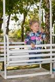 Muchacha adorable feliz del niño en el oscilación en patio cerca de la guardería Montessori Fotografía de archivo