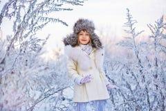 Muchacha adorable feliz del niño en sombrero y capa de piel en bosque del invierno Fotos de archivo libres de regalías