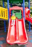 Muchacha adorable feliz en diapositiva del ` s de los niños en patio cerca de la guardería Montessori el día de verano Fotos de archivo