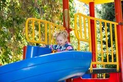 Muchacha adorable feliz en la diapositiva de los niños en patio cerca de la guardería Montessori Foto de archivo
