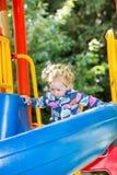 Muchacha adorable feliz en la diapositiva de los niños en patio cerca de la guardería Montessori Fotos de archivo libres de regalías