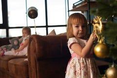 Muchacha adorable que adorna el árbol de navidad con las bolas Imagen de archivo