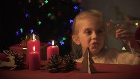 Muchacha adorable que juega con el ángel de madera, centelleo del árbol de navidad, imaginación almacen de video