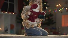 Muchacha adorable que juega con el oso de peluche debajo del árbol de navidad que brilla intensamente, víspera del día de fiesta metrajes