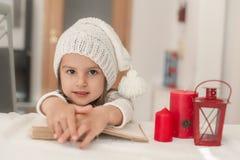 Muchacha adorable que lee un libro y que espera a Santa Claus Imagen de archivo libre de regalías
