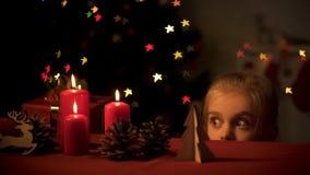 Muchacha adorable que mira secretamente los juguetes de madera, centelleo del árbol de navidad, niñez imagen de archivo libre de regalías