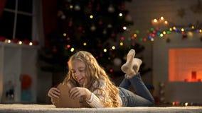 Muchacha adorable que prepara el sobre con la letra a Papá Noel, creencia en magia de Navidad imagenes de archivo