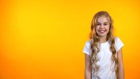 Muchacha adorable que ríe feliz la colocación en fondo, humor y bromas anaranjados imagenes de archivo
