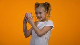 Muchacha adorable que sacude el piggybank, instrucción financiera, depósito para el futuro, ahorros metrajes