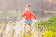 Muchacha adorable que salpica el agua del charco en bosque Fotos de archivo