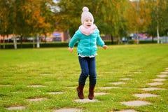 Muchacha adorable que salta en parque del otoño Imagen de archivo libre de regalías